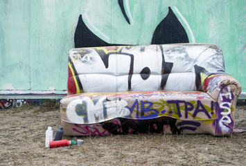 Sofa covered with graffiti on city street
