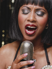 African woman singing into microphone