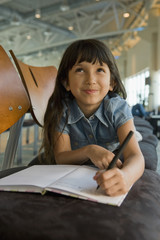 Hispanic girl writing in diary in airport