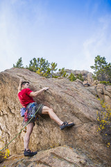 Mixed race climber scaling steep rock face