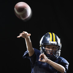 Hispanic boy in football uniform throwing ball