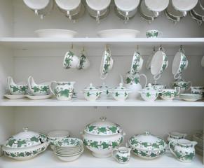 Matching ceramic dinnerware on shelves