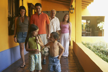 Multi-generational family standing on porch