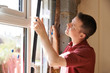 Construction Worker Installing New Windows In House - 82163255