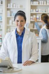 Hispanic pharmacist working at counter