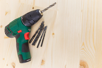 Electric drill and drill bits on a wooden background horizontal