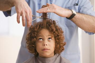 Mixed Race boy getting haircut