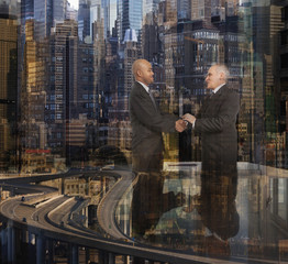 Businessmen shaking hands over skyscrapers