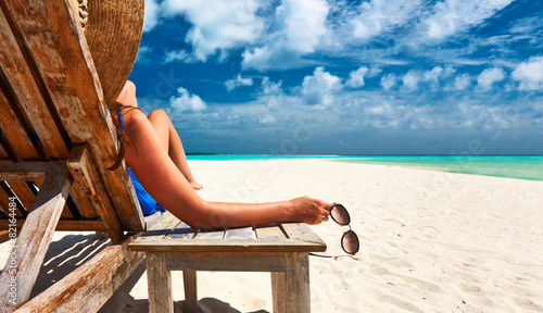 canvas print picture Woman at beach holding sunglasses