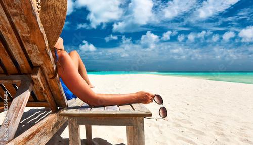 Leinwanddruck Bild Woman at beach holding sunglasses