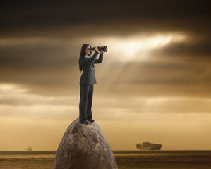 Caucasian businesswoman with binoculars on rock in ocean