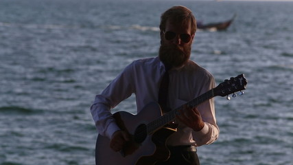 guitarist in shirt plays against sea and longtail boats