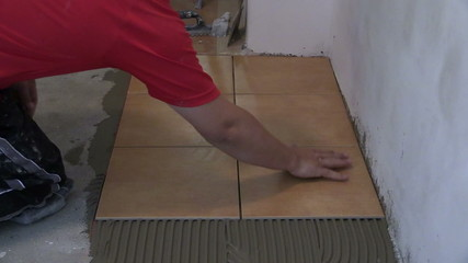 Construction worker is tiling floor at home. Static shot