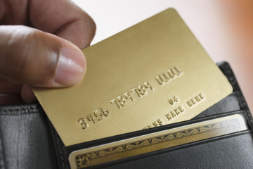 Mixed Race man taking credit card out of wallet