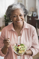 Black woman eating bowl of salad