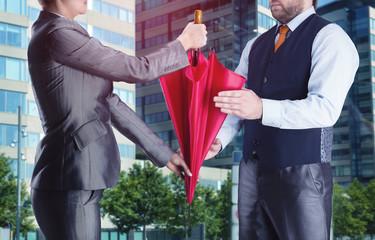 Businesswoman gives umbrella to businessman