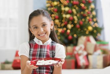Hispanic girl holding plate of Christmas cookies