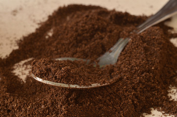 Spoon in light dark powder of coffee