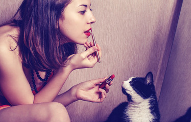 The girl paints lips with lipstick looking in the mirror