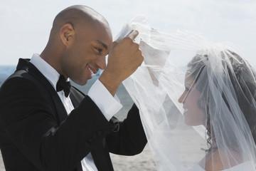 African groom lifting bride's veil