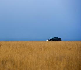 Car driving along rural field
