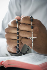 Mixed Race man holding rosary