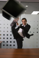 Businessman kicking laptop