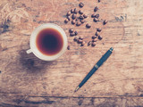 Cup of coffee with beans and a pen