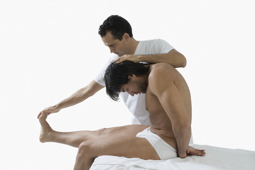 Chiropractor adjusting man's back