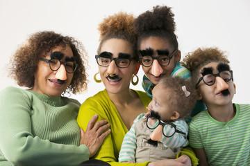 Three generations of Black women wearing disguises
