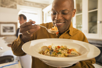 African American man eating seafood stew