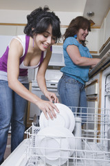 Young woman helping mother load dishwasher