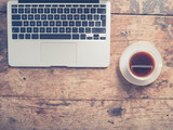 Laptop and cup of coffee on table © LoloStock