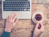 Man using laptop and having coffee