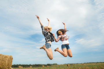 Funny air jump of two college friends on summer rural vacations