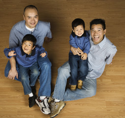 Asian fathers holding sons in lap