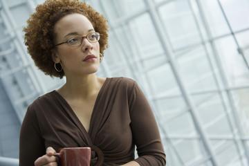 African businesswoman holding coffee mug