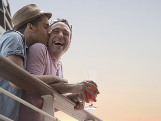 Gay couple having drinks on cruise ship deck