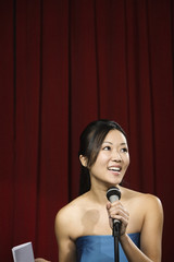 Asian woman speaking into microphone on stage