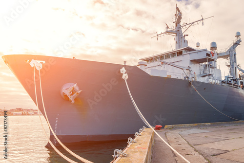 Naval auxiliary ship docked at the harbor. - 82173494