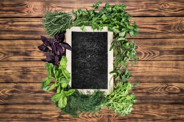 Herbs. Blank green blackboard with variety fresh herbs over