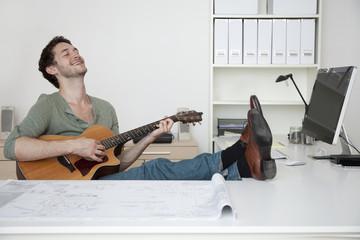 Caucasian businessman playing guitar at desk