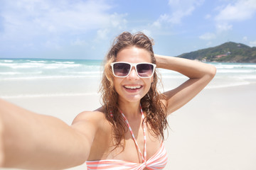 Beautiful young woman doing selfie on the beach