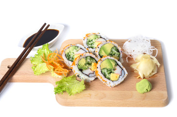 Set of California sushi rolls on a wooden board with chopsticks
