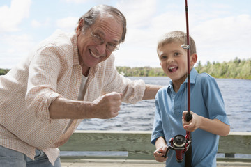 Older Caucasian man fishing with grandson