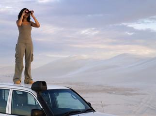 Mixed Race woman looking through binoculars