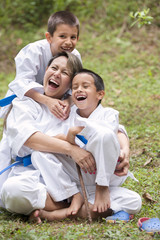 Hispanic family wearing martial arts robes in grass