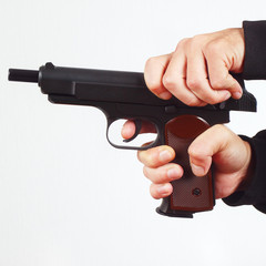 Hands reload semi-automatic gun on a white background