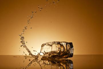 падающий стакан с виски на золотом фоне