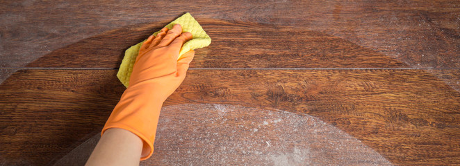 Cleaning soiled parquet in gloves